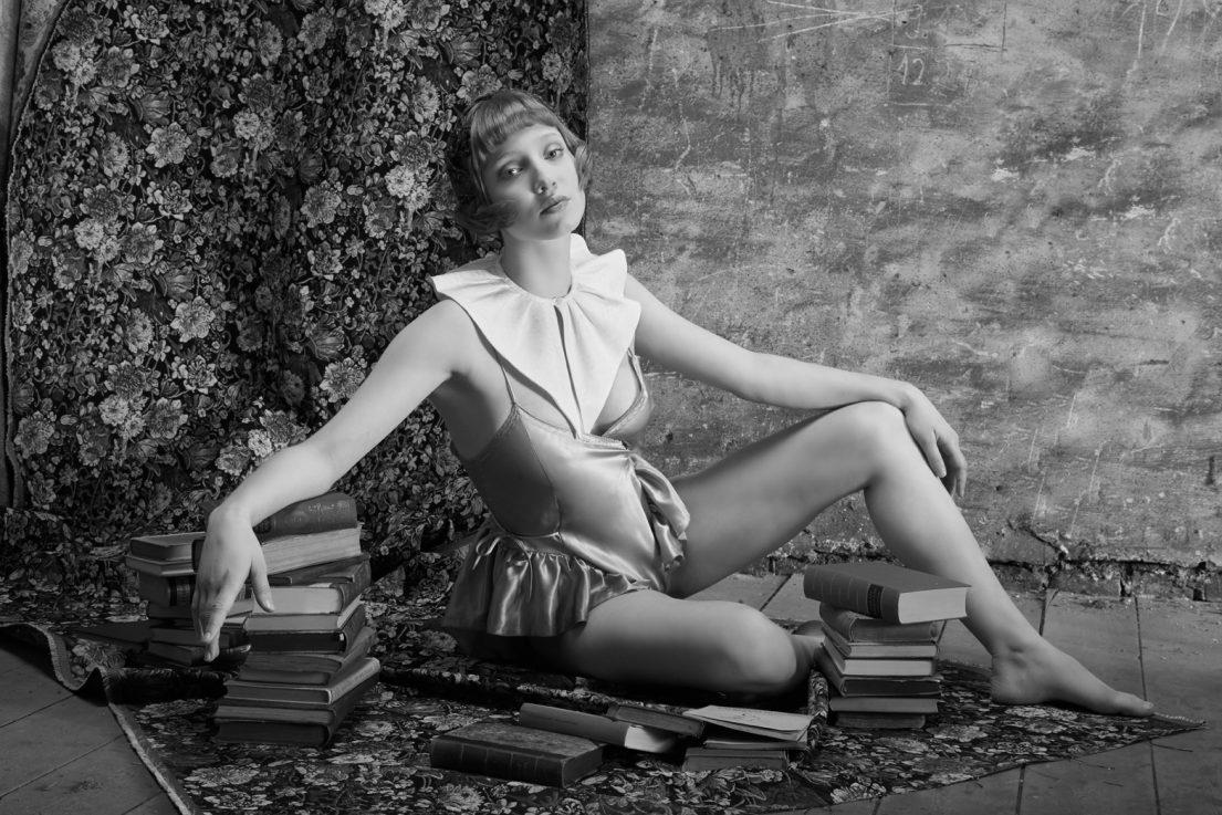 weibliches model mit fashion der golden 20s sitz auf boden abgestützt auf bücherstpel