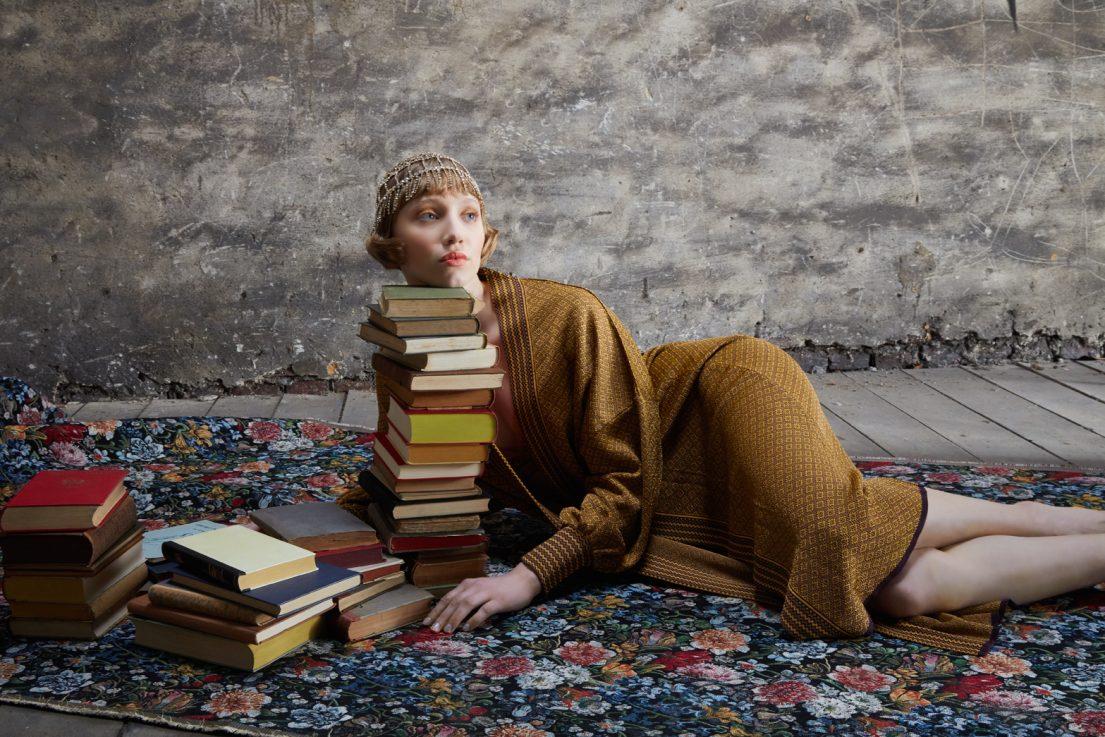 weibliches model mit fashion der golden 20s liegt auf boden mit teppich und büchern
