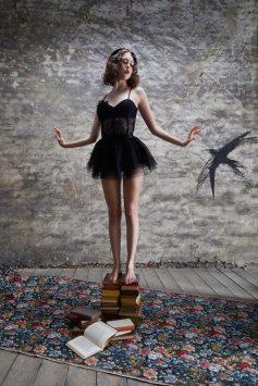 weibliches model mit fashion der golden 20s steht auf bücherstapel