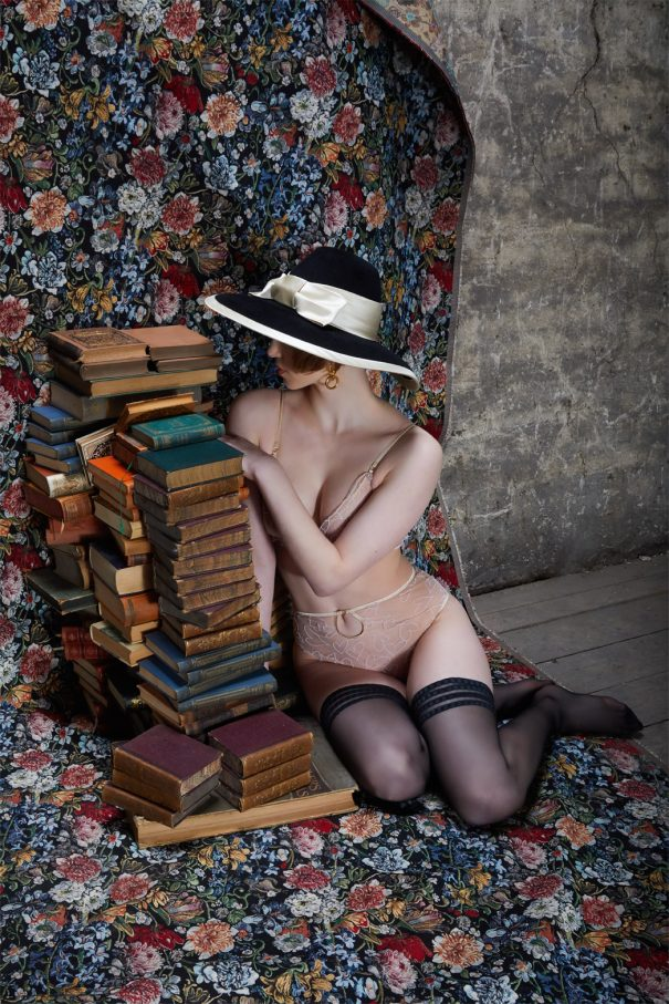 weibliches model mit fashion der golden 20s sitz auf tepich an stapel büchern